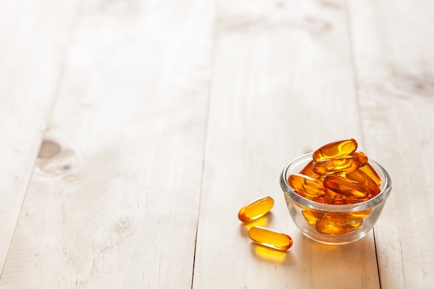 Fish oil in a jug and capsules on wooden texture and table