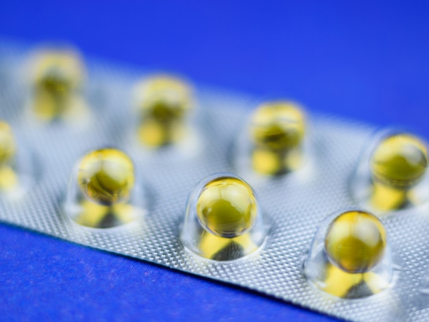 Fish oil pills in a blister on a blue table