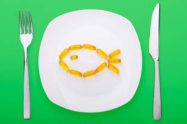 魚の形の白い磁器プレートの上に横たわる魚油ソフトゲル