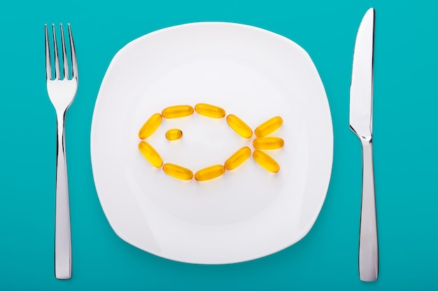 Fish oil soft gels lying on white porcelain plate in the form of fish