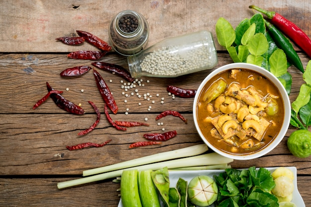 Fish organ sour soup with cashew nut and other ingredients on wooden background.