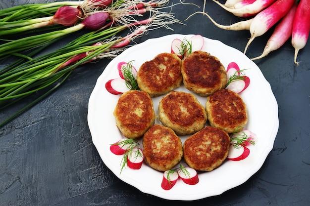 Рыбные котлеты на белой тарелке на темном фоне, а также овощи: редис и зеленый лук.