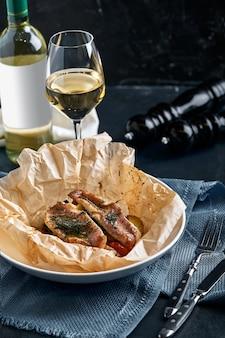 皿にクラフト紙でフィッシュパイと野菜、レストランを与える。素朴なスタイル。セレクティブフォーカス。