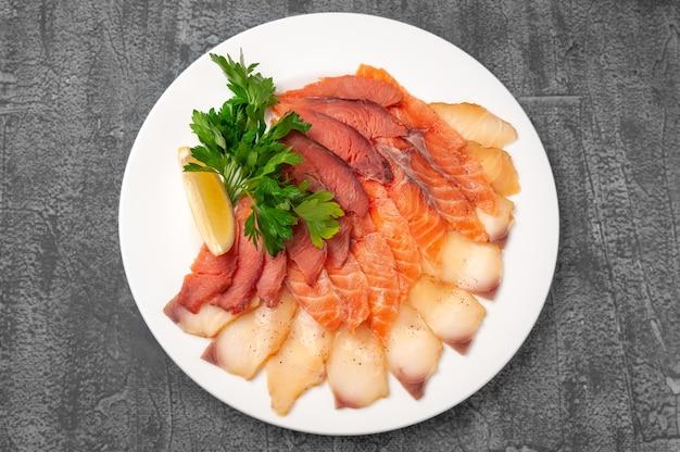 Рыбное ассорти из лосося и жирной рыбы. на большой белой тарелке. украшается долькой лимона и зеленью. вид сверху. на сером фоне бетона.