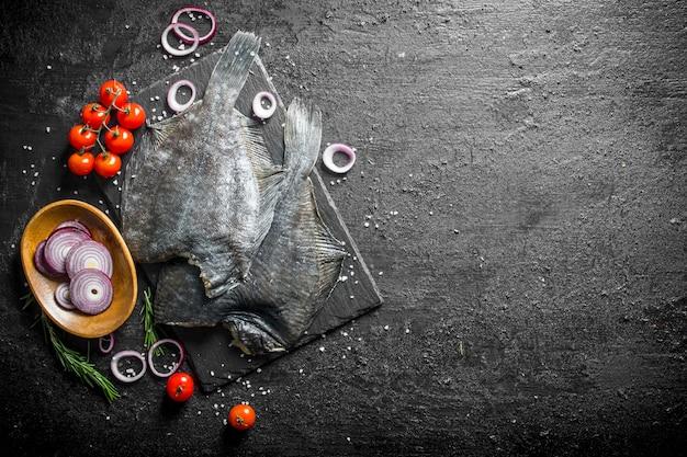 黒い素朴なテーブルの上にトマトとオニオンリングと魚の生のヒラメ