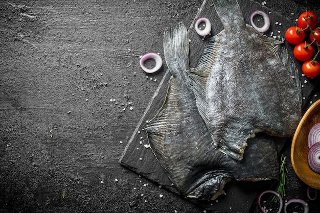 Рыба сырая камбала с помидорами и луковыми кольцами. на черном деревенском