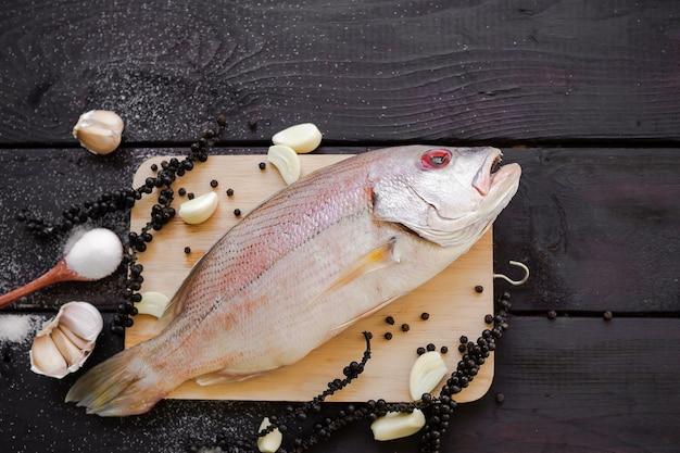 調理済みの料理人と一緒に魚のローフードは、ニンニクとコショウで揚げたタイ料理の材料です。