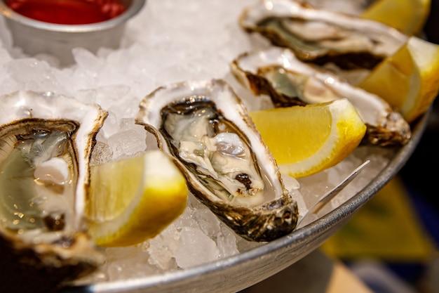 魚料理店。生牡蠣、レモン、ソースを氷と一緒にトレイに