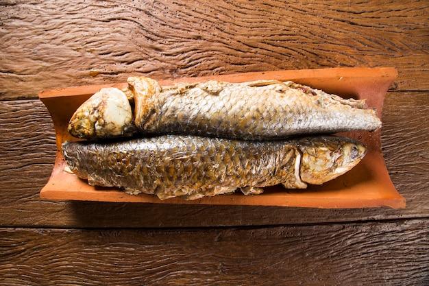 오래 된 나무 테이블에 타일에 구운 생선