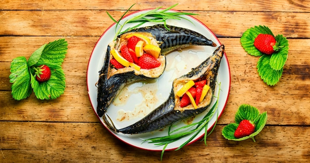 Fish roasted with strawberry and lemon.summer fish dish,baked mackerel on wooden table