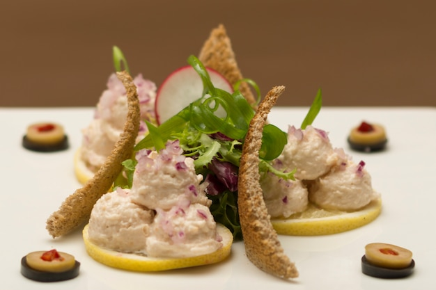 Fish roe salad with toasted bread, onion, green leafs, lemon, radish and olives, white pla