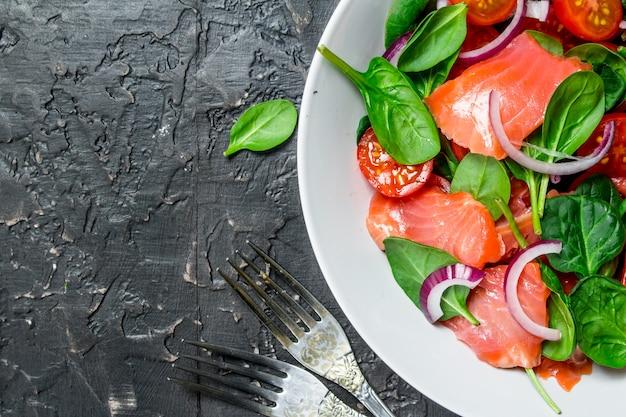 魚のサラダ。サーモン、トマト、ほうれん草のスライスとライムジュースのサラダ。