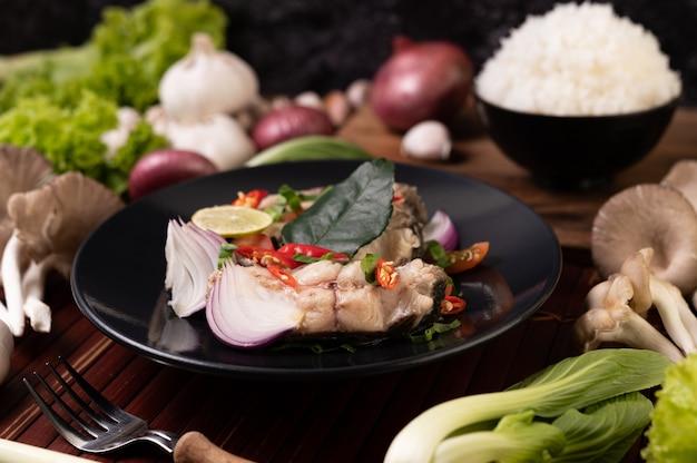 プレートにライム、チリ、レモングラス、玉ねぎ、赤玉ねぎ、パセリ、カフィアライムの葉を添えた魚のサラダ