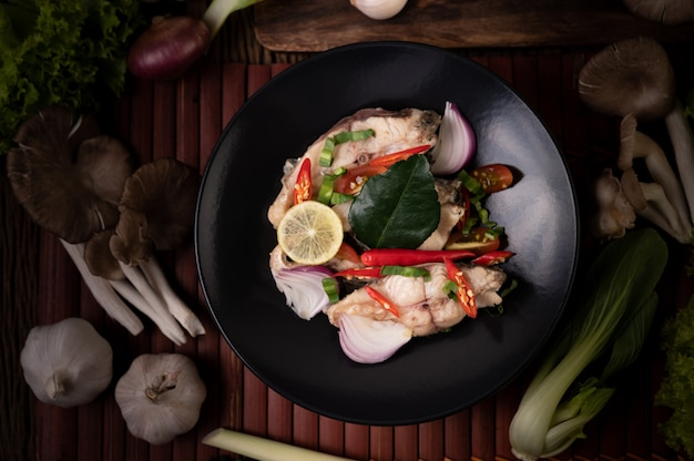 접시에 라임, 칠리, 레몬 그라스, 양파, 적 양파, 파슬리, 카피 르 라임 잎이 들어간 생선 샐러드
