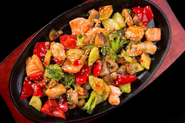 Fish salad with salmon pieces, vegetables, mushrooms and sesame, in a pan, on a black surface