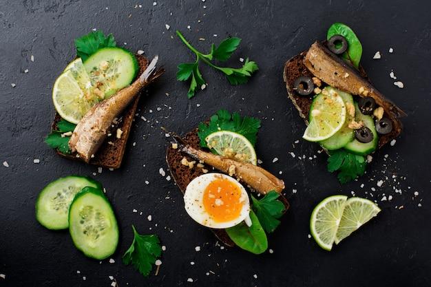 Рыбные бутерброды со шпротами, огурцом, лаймом, вареными яйцами, листьями петрушки и мангольдом на ржаном хлебе на старом черном бетоне
