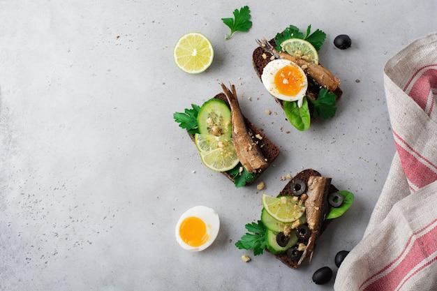 Рыбные бутерброды со шпротами, огурцом, лаймом, вареными яйцами, листьями петрушки и манго на ржаном хлебе на сером старом бетонном или каменном фоне. выборочный фокус. деревенский стиль. вид сверху. скопируйте пространство.