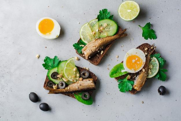 Рыбные бутерброды со шпротами, огурцом, лаймом, вареными яйцами, листьями петрушки и манго на ржаном хлебе на сером старом бетонном или каменном фоне.