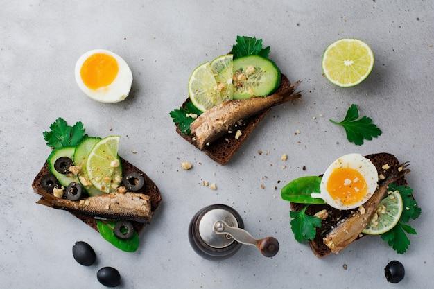 灰色の古いコンクリートまたは石の表面のライ麦パンに、スプラット、キュウリ、ライム、ゆで卵、パセリの葉、マンゴーを添えた魚のサンドイッチ。セレクティブフォーカス。素朴なスタイル。上面図。