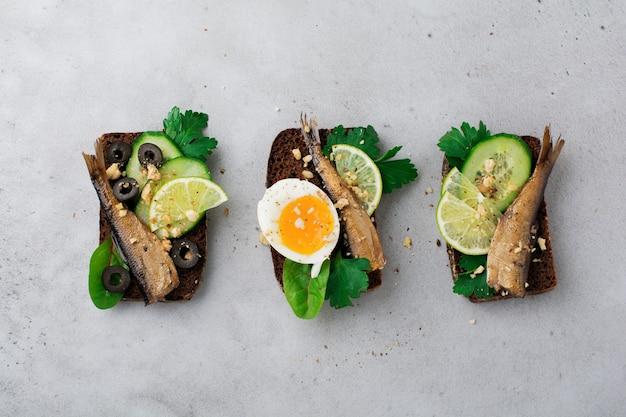 Рыбные бутерброды со шпротами, огурцом, лаймом, вареными яйцами, листьями петрушки и манго на ржаном хлебе на старом сером бетоне. селективный фокус