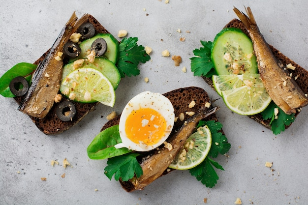 灰色の古いコンクリートの表面のライ麦パンに、スプラット、キュウリ、ライム、ゆで卵、パセリの葉、マンゴーを添えた魚のサンドイッチ。セレクティブフォーカス