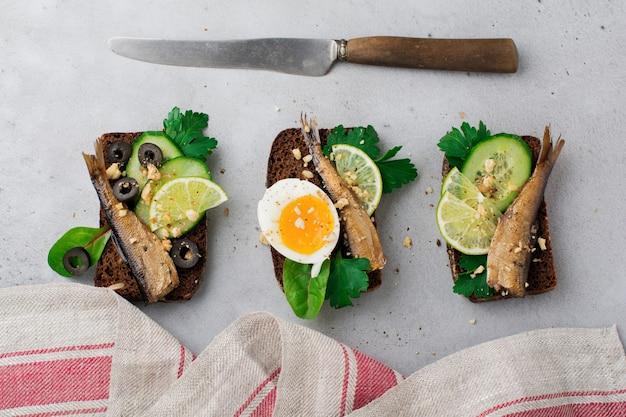 Рыбные бутерброды со шпротами, огурцом, лаймом, вареными яйцами, листьями петрушки и манго на ржаном хлебе на сером старом бетоне