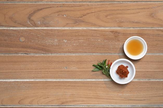 Рыбный соус с специями таиланда в белом чашке на дереве, для приготовления тайских продуктов