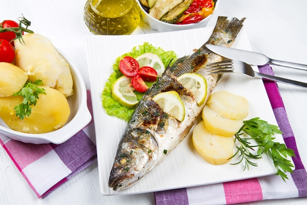 Fish, sea bass grilled with lemon, salad and potatoes