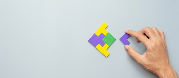 회색에 다채로운 나무 퍼즐 조각의 물고기 모양 블록.