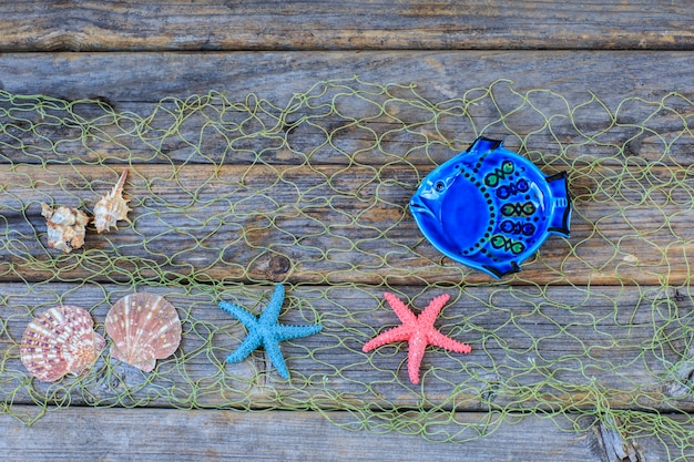 Fish, shells, starfish in the net on a wooden background.