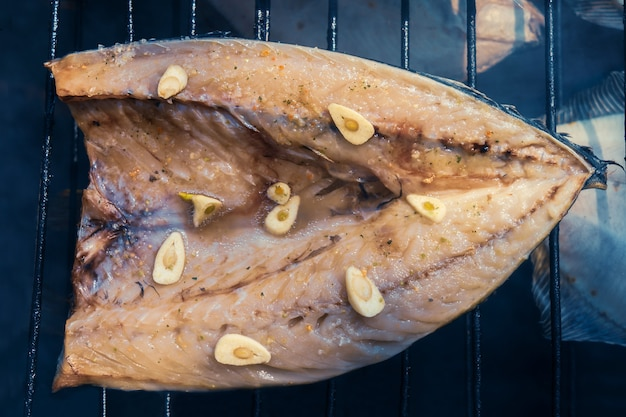 Процесс копчения рыбы. копченая скумбрия на решетке. закройте курить. вид сверху