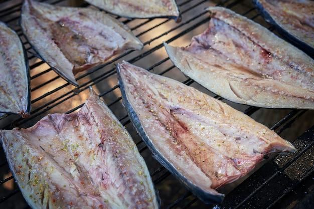 Процесс копчения рыбы. копченая скумбрия с зеленью и чесноком. закройте курить. вид сверху, выборочный фокус