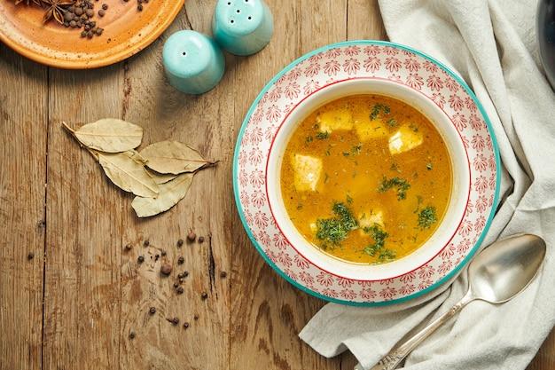 Рыбный суп в красном шаре на деревянной поверхности. здоровый суп из морепродуктов, ресторанное обслуживание. уха