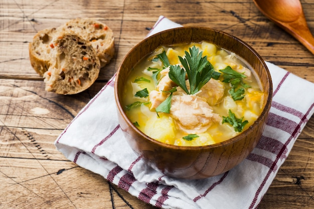 Рыбный суп в деревянной миске со свежей зеленью.