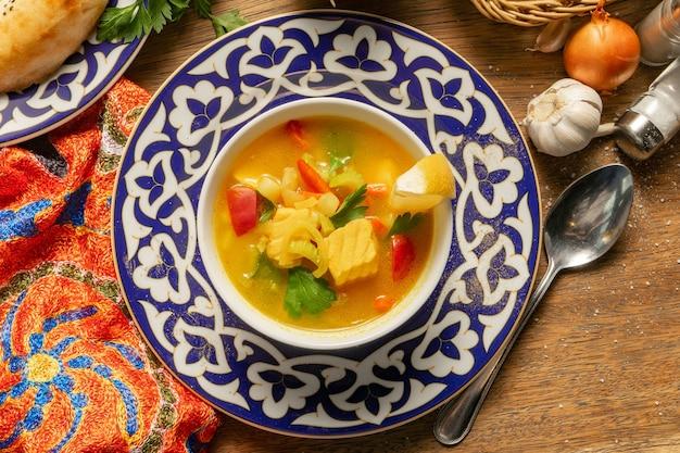 Уха из лосося, лука, помидоров, чеснока, моркови, картофеля, укропа, специй и лимона в тарелке с традиционными узбекскими орнаментами.