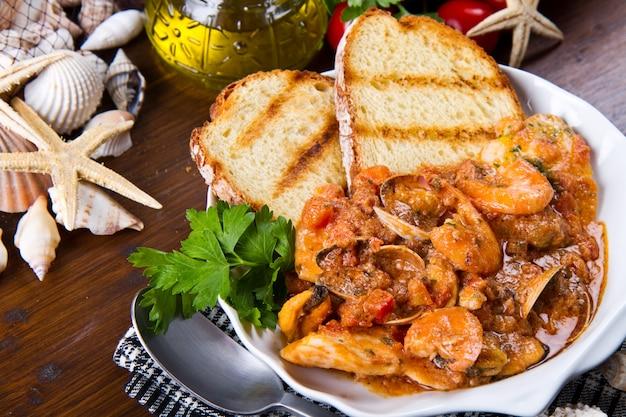 돼 먹지 못한 냄비에 구운 btread와 생선 수프
