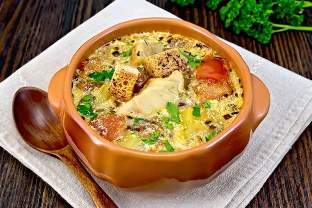Рыбный суп с помидорами, картофелем, перцем и сливками в глиняной миске на салфетке, петрушка на темном фоне деревянной доски