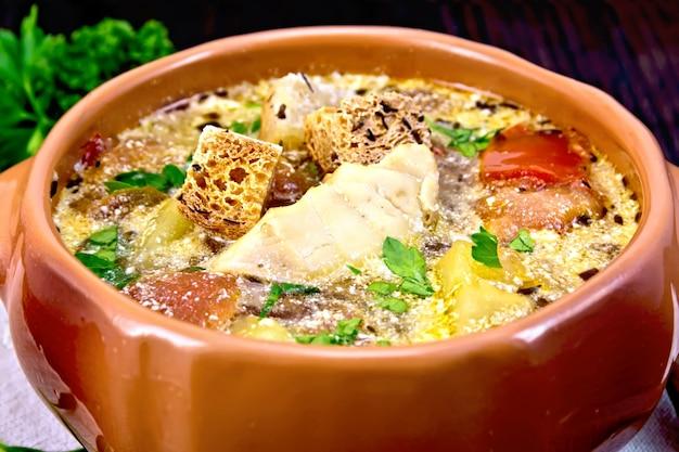 Рыбный суп с помидорами, картофелем, перцем и сливками в глиняной миске на салфетке, петрушка на фоне деревянной доски