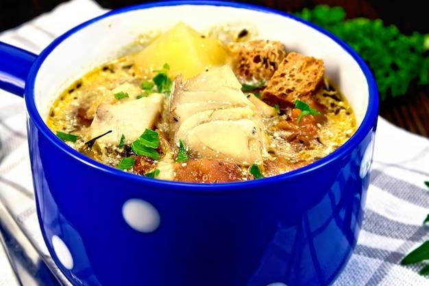 Рыбный суп с помидорами, картофелем, перцем, гренками и сливками в синей миске на полотенце, петрушка на фоне деревянной доски
