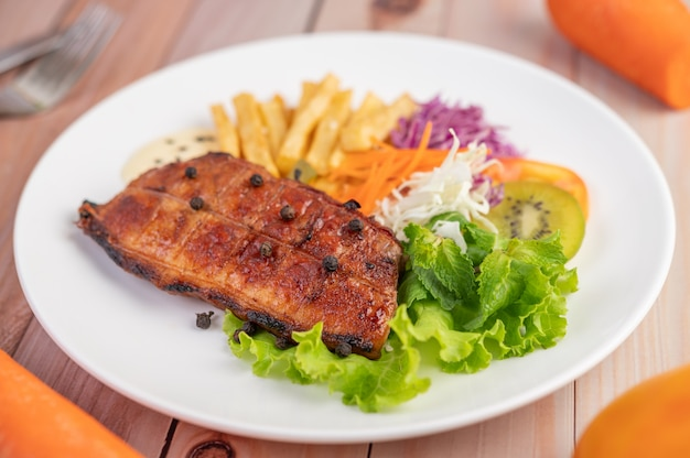 Fish steak with french fries, kiwi, lettuce, carrots, tomatoes, and cabbage in a white dish.