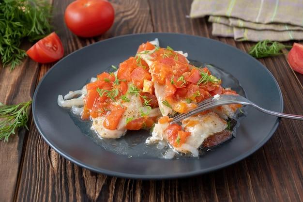 Тушеная рыба с помидорами и укропом на тарелке на деревянном столе
