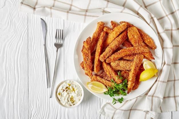 魚のスティック、パン粉をまぶして揚げた魚の切り身の指を、タルタルソースとレモンのくさびを添えた木製のテーブルの白いプレートに載せ、上からの水平方向の眺め、平らな場所の空きスペース
