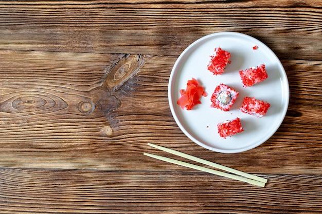 Рыба суши роллы лосось красная икра палочки для еды серые керамические сервировочные тарелки деревянный фон. морепродукты