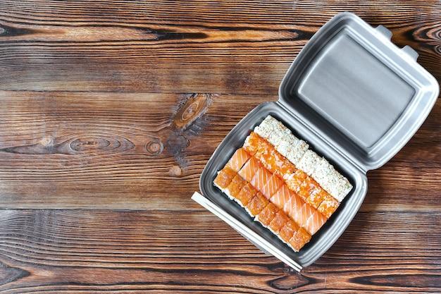サーモンとゴマを使い捨ての食品容器に詰めた魚巻き寿司。シーフード、食品配達