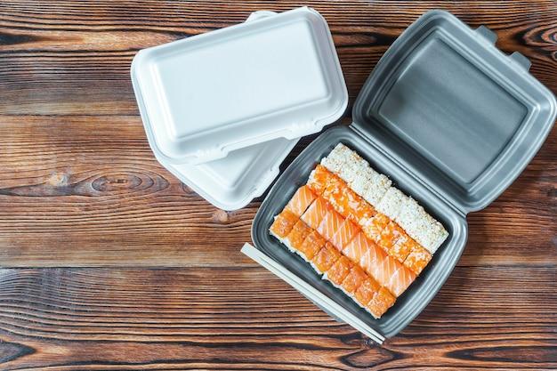 木製の素朴な背景にプラスチックの使い捨て食品容器に詰められたサーモンとゴマの魚巻き寿司。シーフード、レストランのコンセプトからのフードデリバリーサービス、フラットレイ。