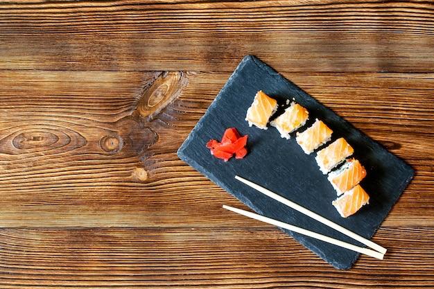 Рыбные суши-роллы с лососем, васаби и палочками для еды на черной разделочной доске. seafoo