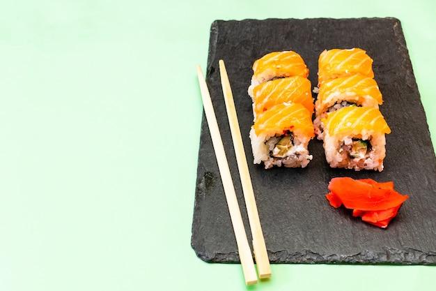 Рыбные суши-роллы с лососем, васаби и палочками для еды на черной сервировочной доске. морепродукты, общественное питание