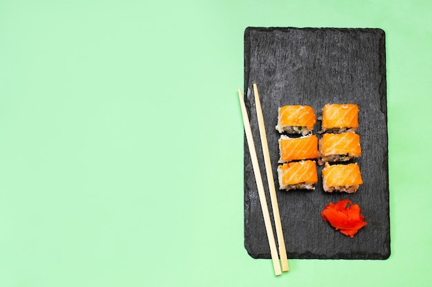 Fish sushi rolls with salmon, wasabi and chopsticks on black cutting serving board on green. seafood