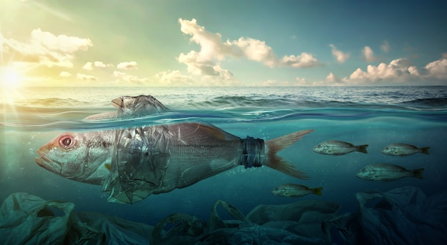 Fish swims among plastic ocean pollution. environment concept