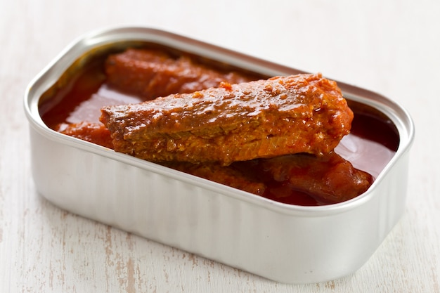Fish in tomato sauce in iron box on white